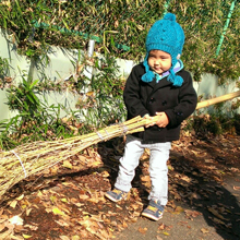 Children cleaning the forest with adult size broom